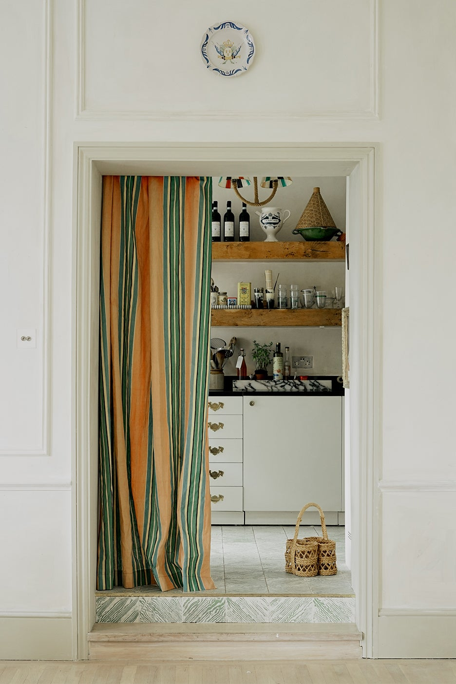 White kitchen behind yellow and green curtain