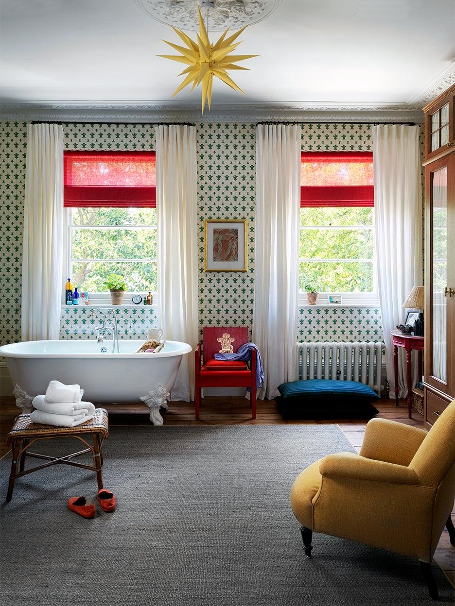 Bathroom with red window shades and clawfoot tub