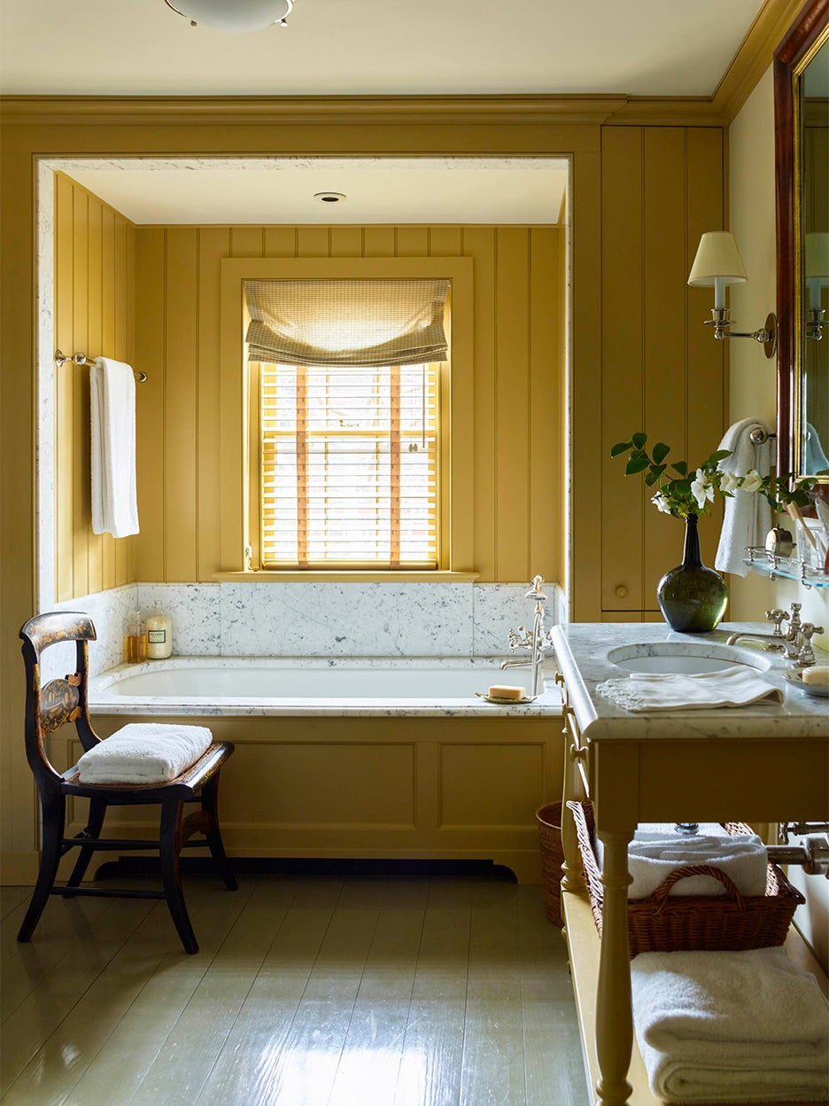 Yellow bathroom with marble tub