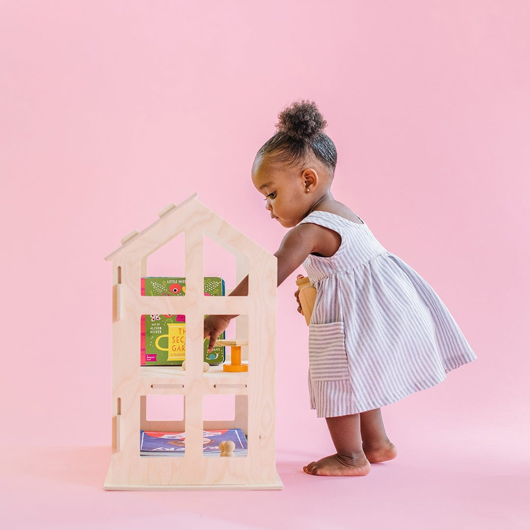 Little girl paying with dollhouse