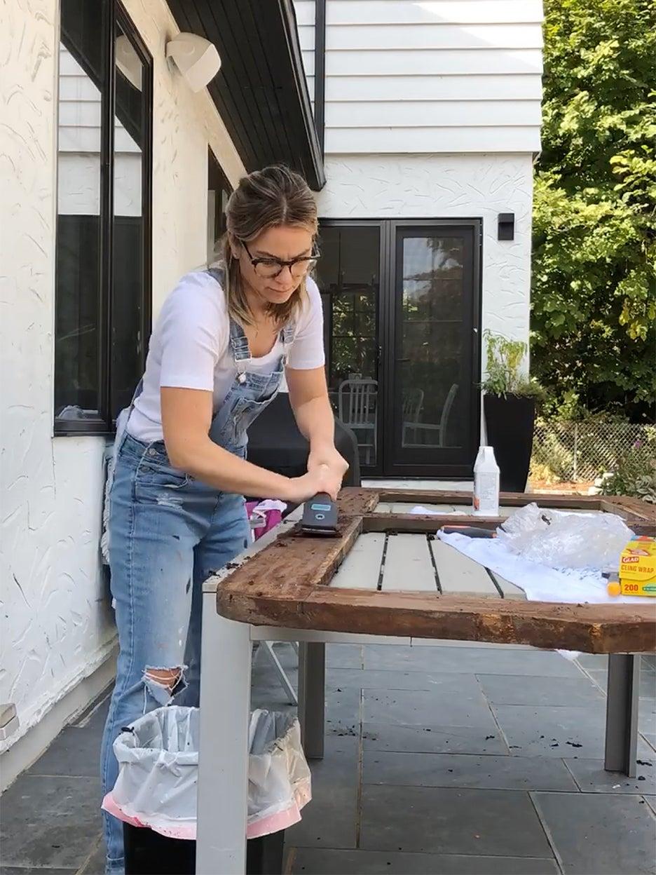woman scraping door on table