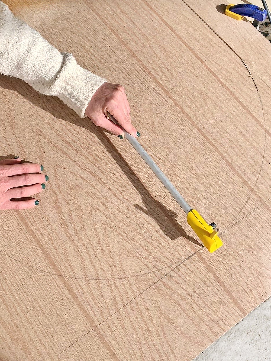 woman drawing curve on wood