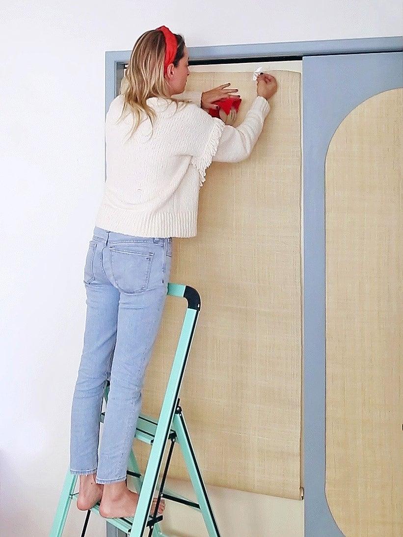 woman hanging fabric on door