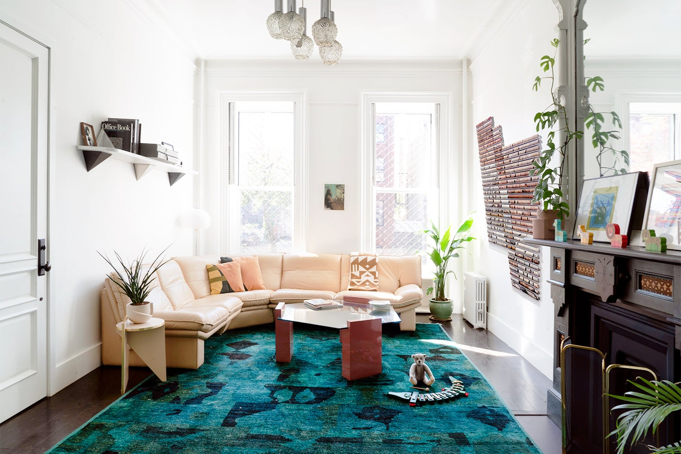 Living room with green rug and beige leather sectional