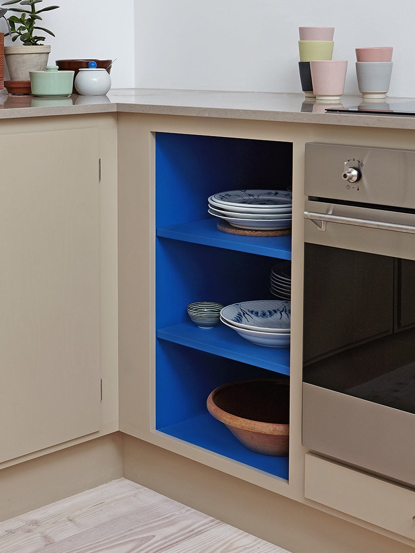 Small kitchen with cobalt blue painted shelves.