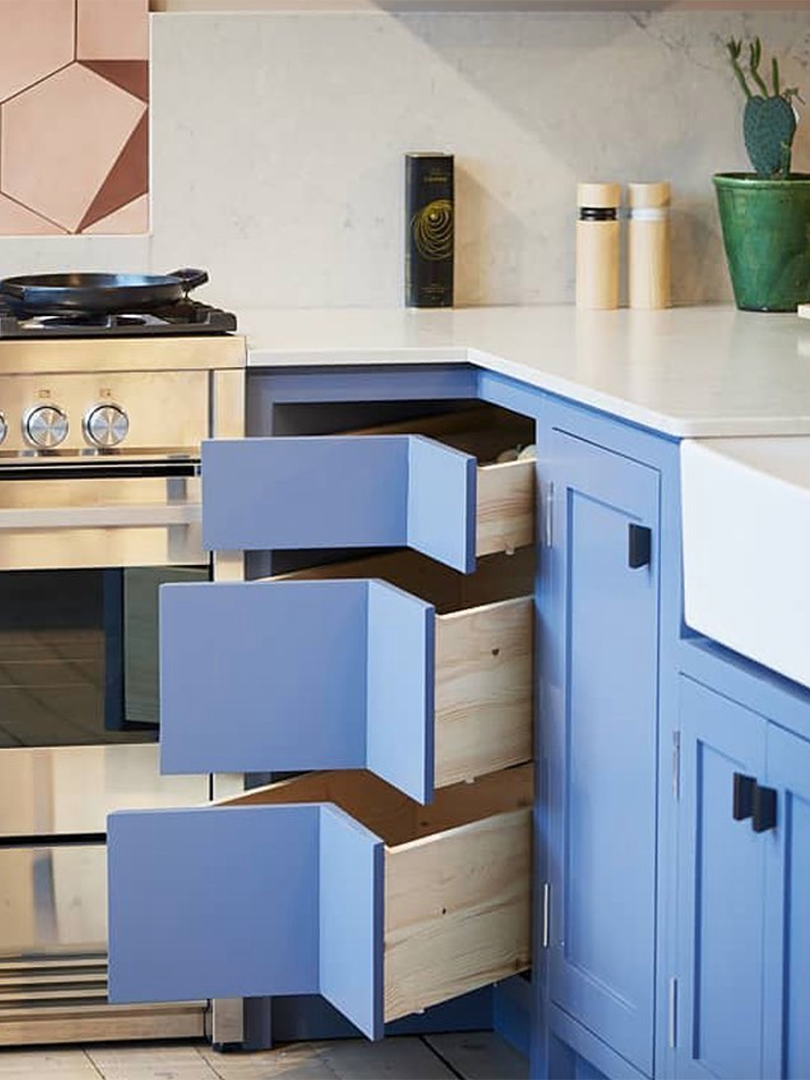 Small kitchen with blue corner drawers.