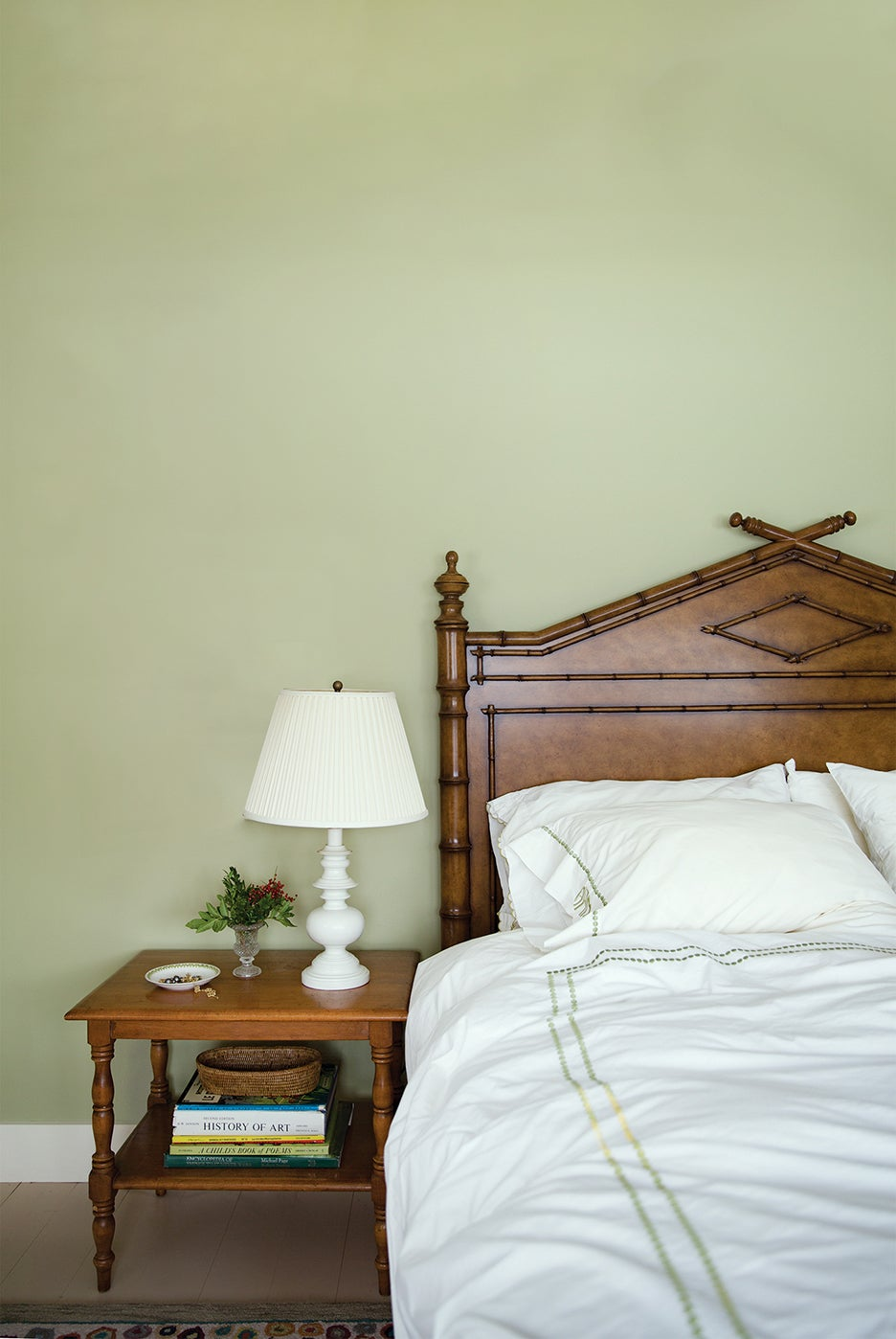 Sage green wall in front of bed