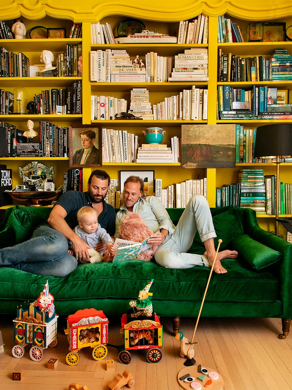 Two men sitting on green velvet couch with their baby.