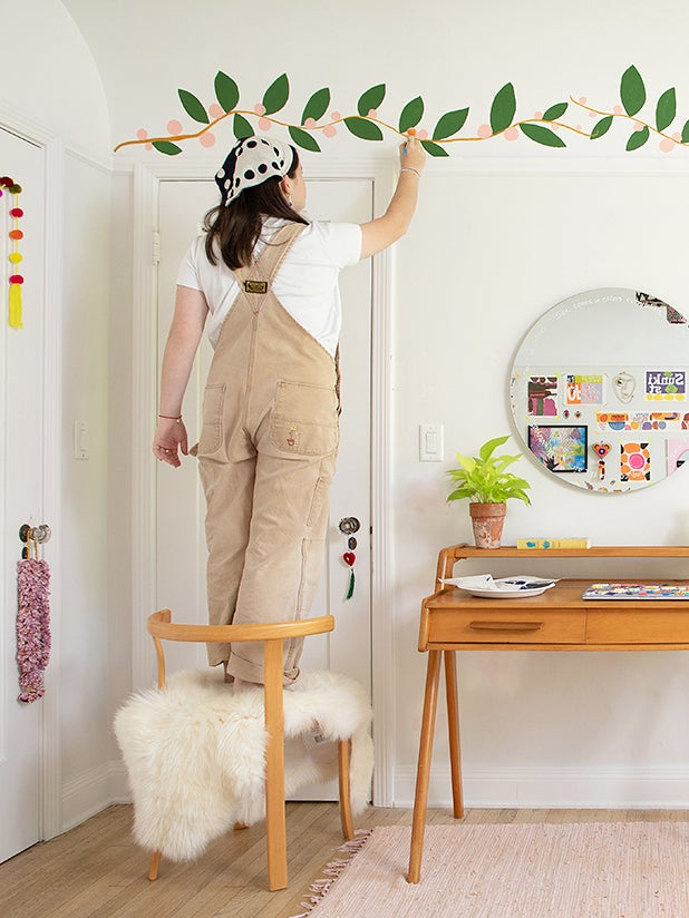Teen girl stands on chair and paints her wall with flowers and vines.