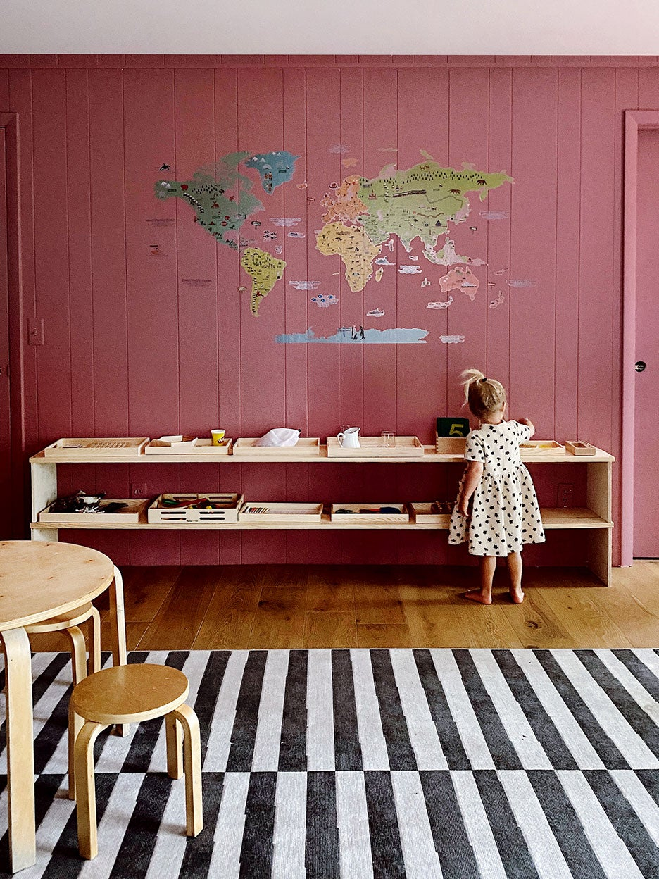 Little girl faces mauve wall with wood shelves and world map decal.