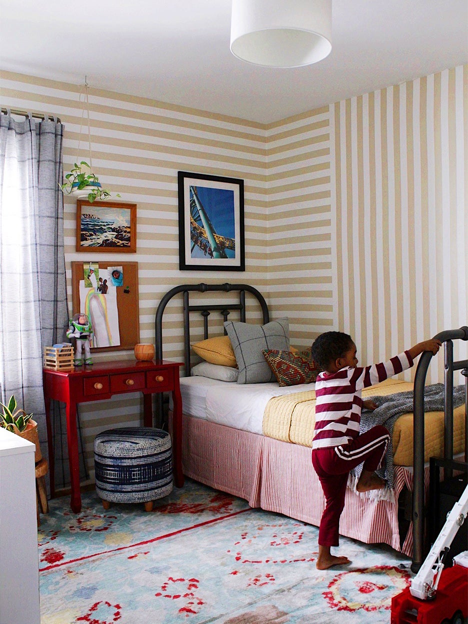 Boy climbing up on his bed with striped beige walls behind him.