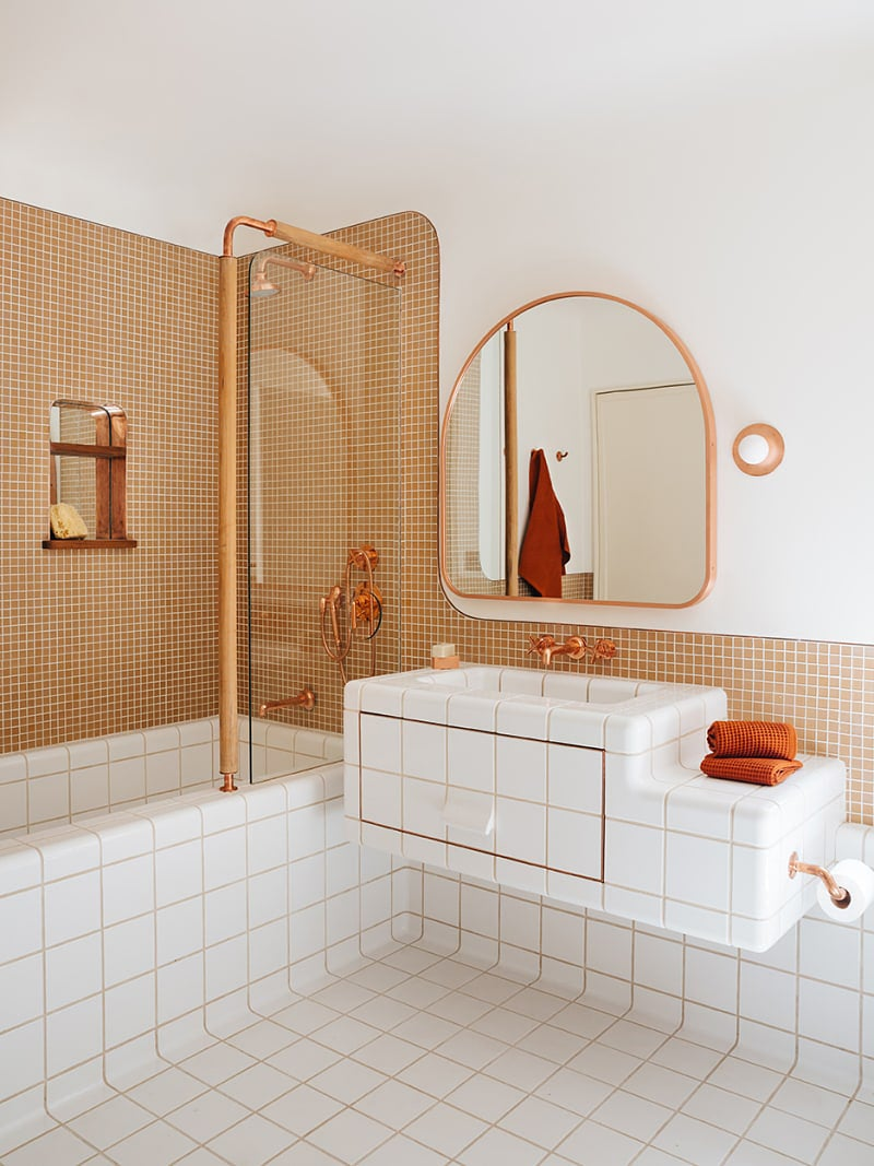 copper toned bathroom with white tile floors