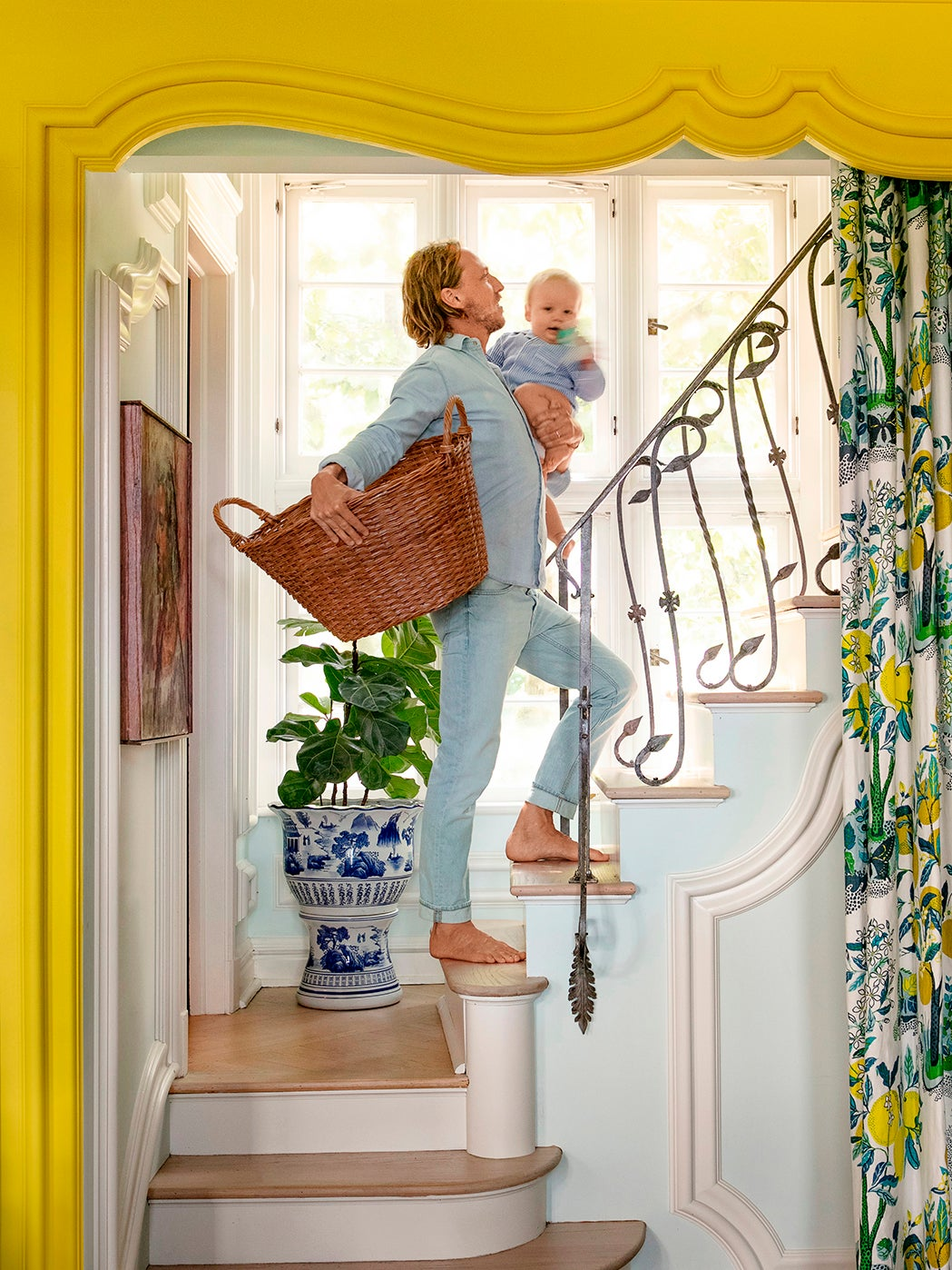 Man on stairs holding baby and laundry basket.