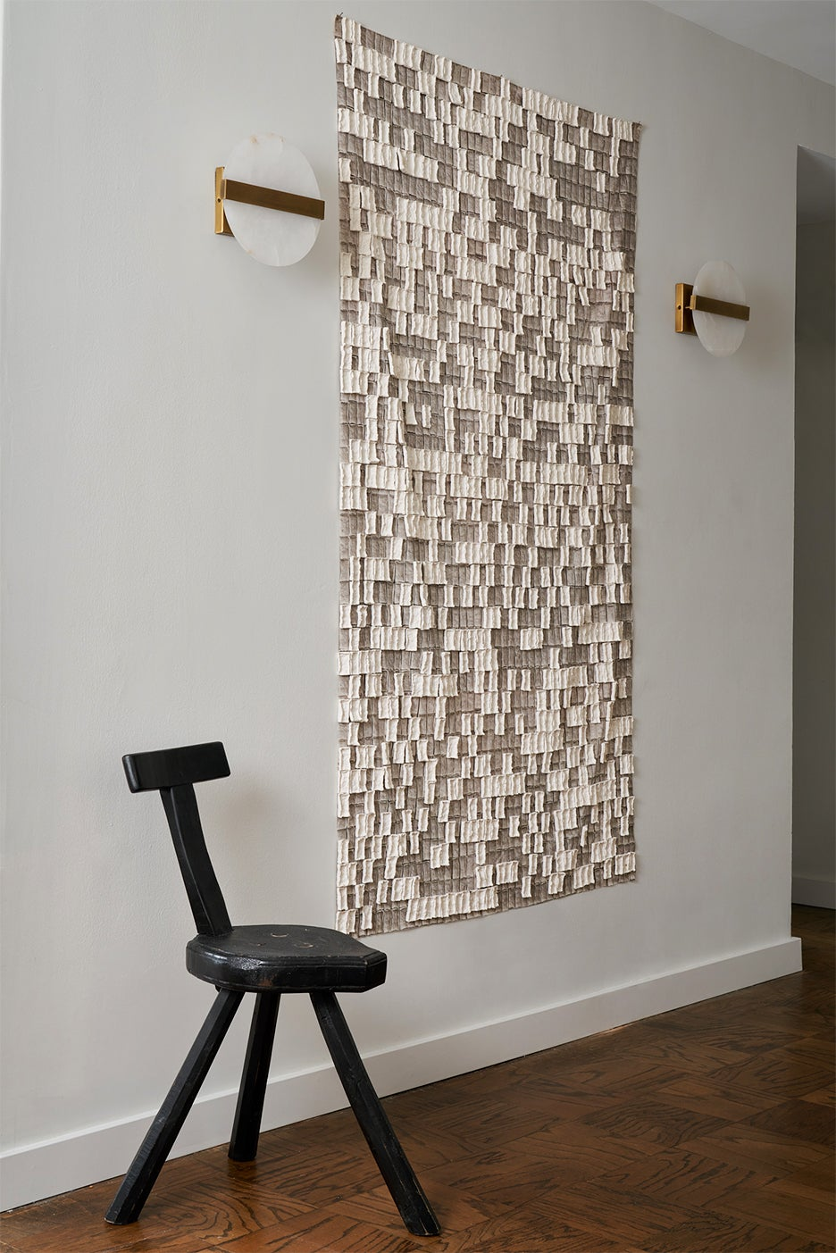 Entryway with tapestry and alabaster wall sconces