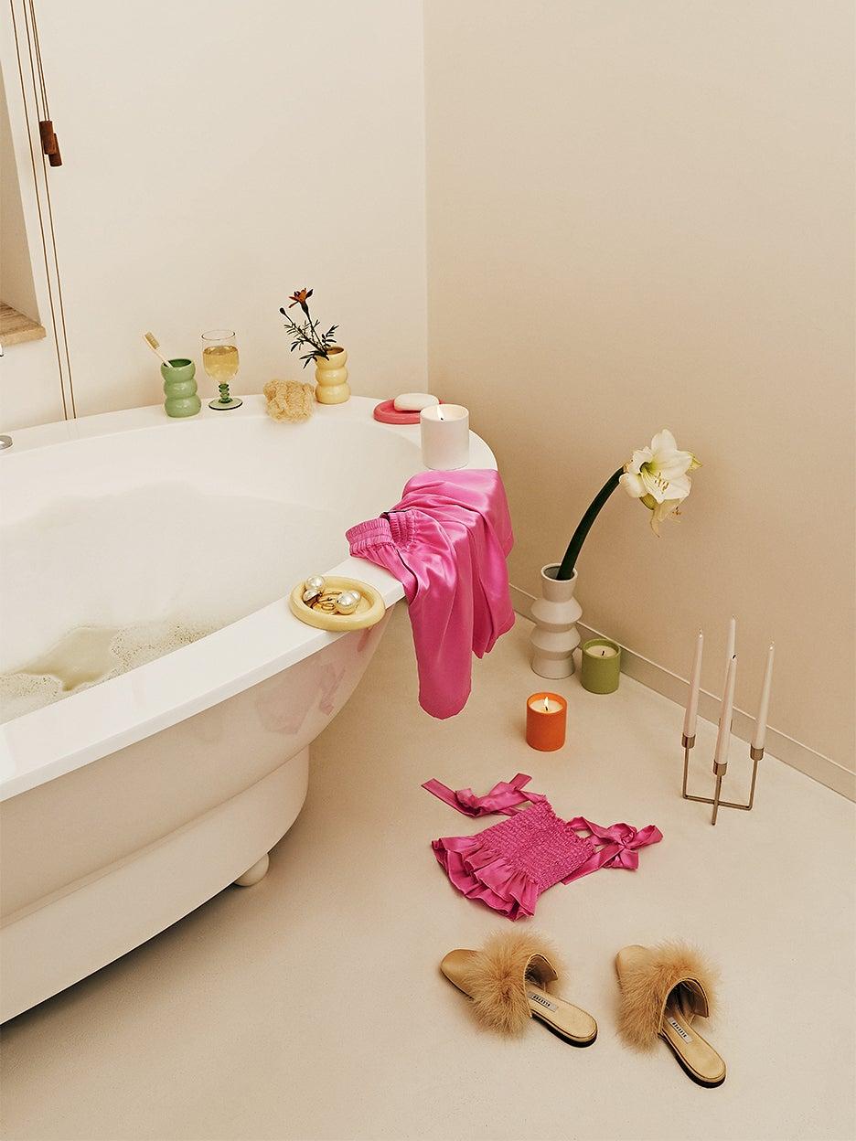 Bath tub with candlesticks, ceramic vases, and silk pajamas