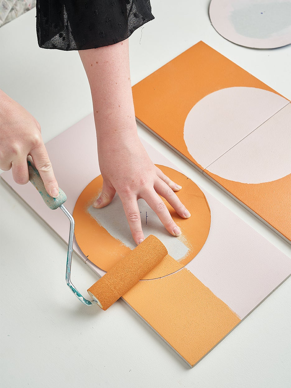person rolling paint on tile