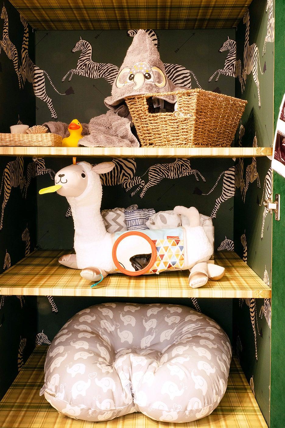 Nursery shelves lined in zebra wallpaper