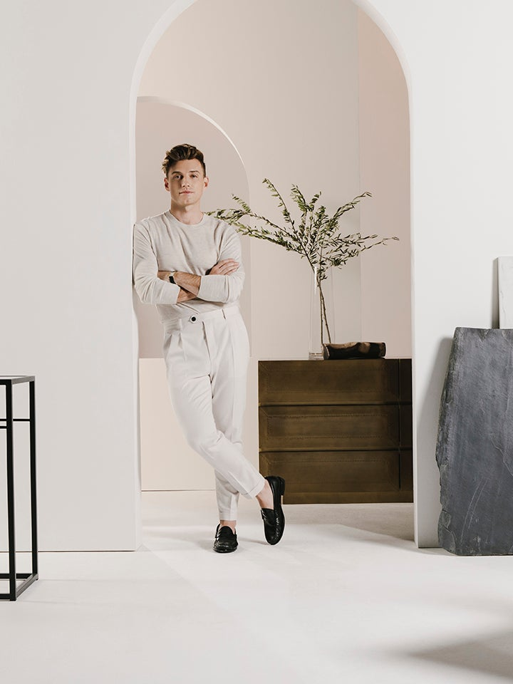Nate Berkus leaning in a doorway wearing all white