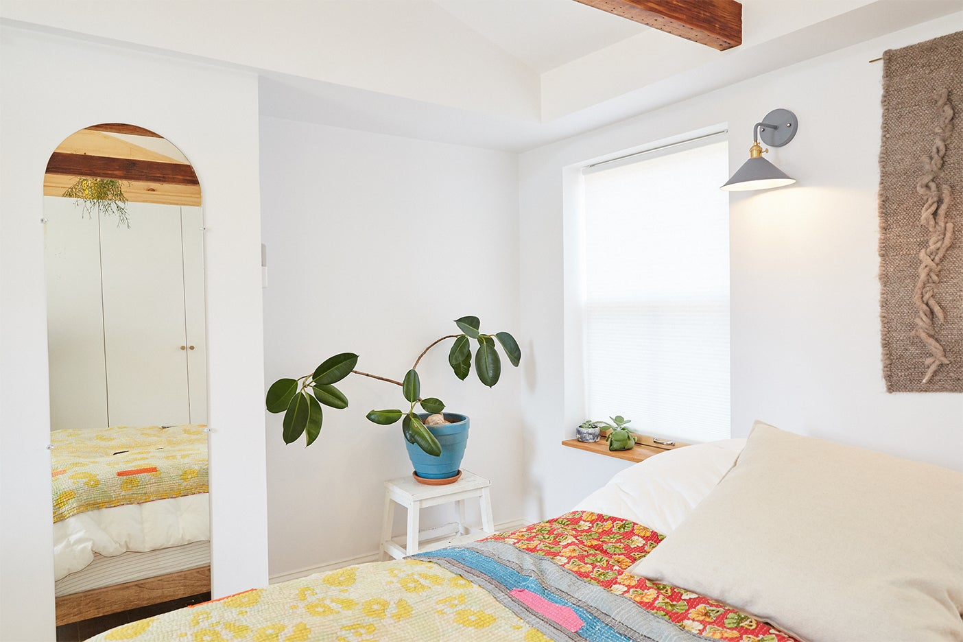 white bedroom with plant on table