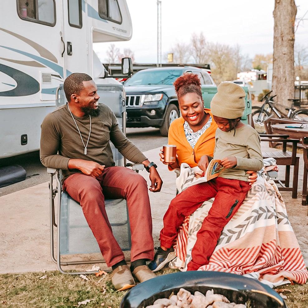 family sitting outside of RV