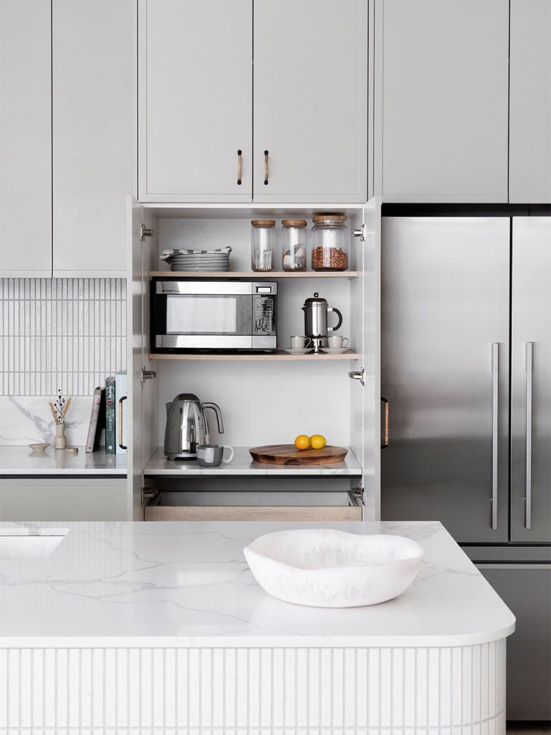 grey kitchen with open appliance cabinet doors