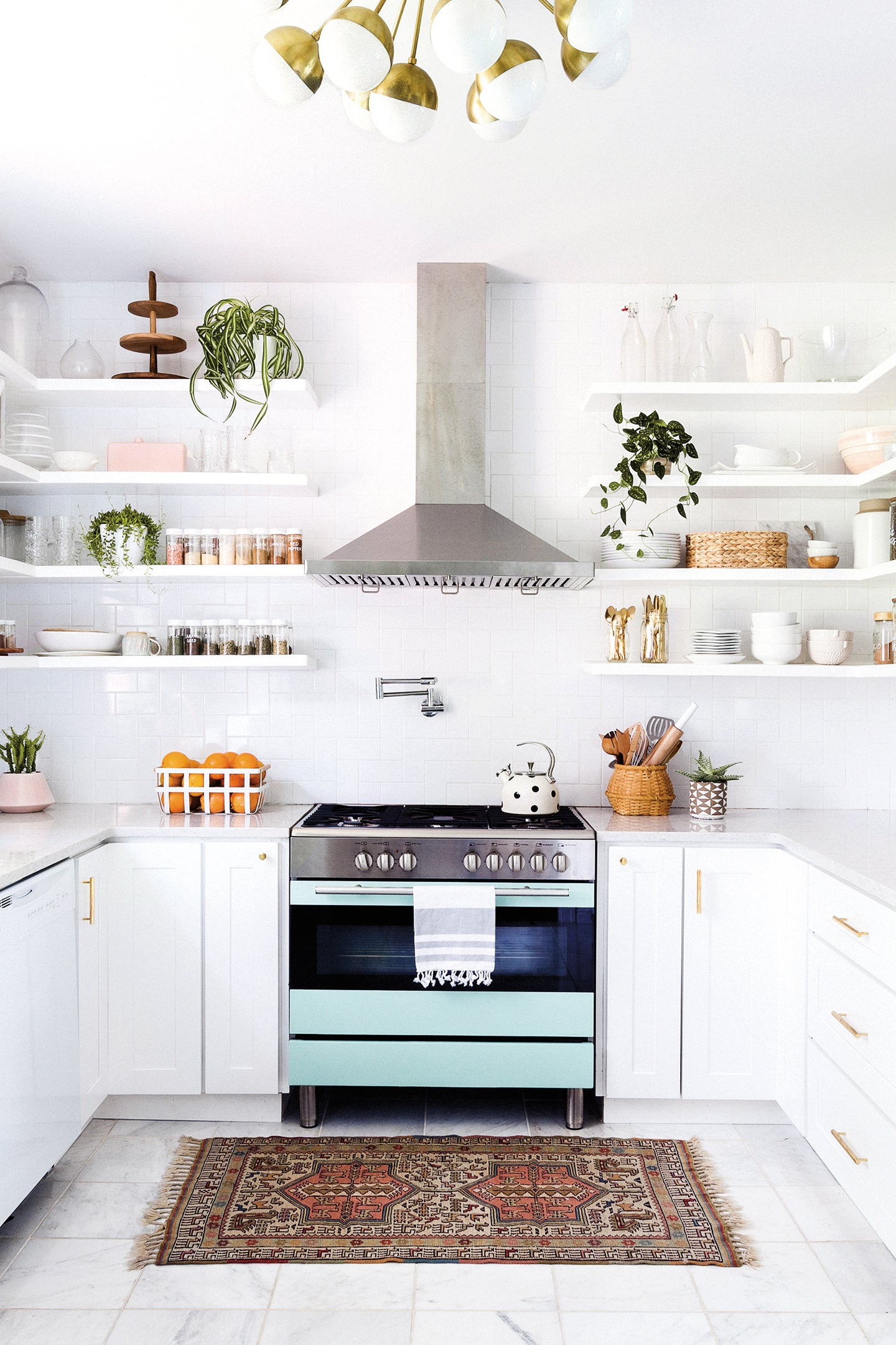 White kitchen with blue oven and open shelving