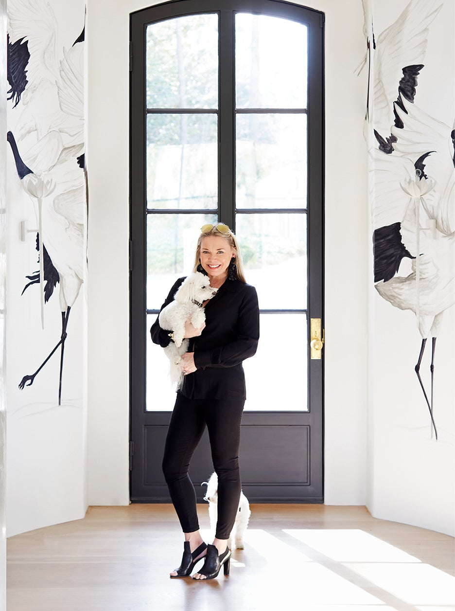 woman holding dog in front of a door