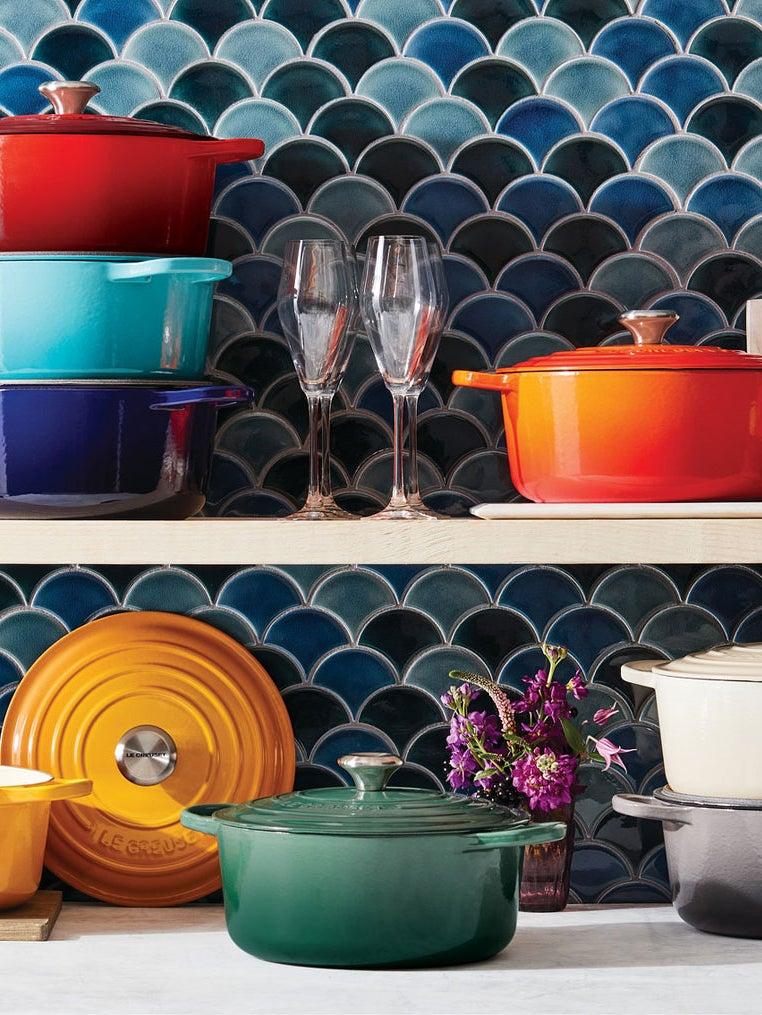 Colorful Le Creuset Dutch ovens on a shelf