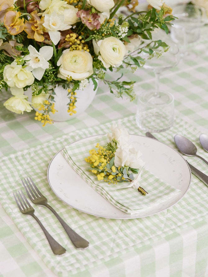 Light green gingham tablecloth layered with matching placemat and napkin