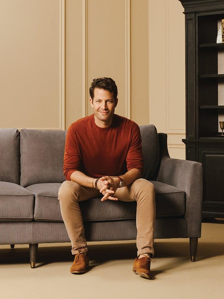 Nate Berkus sitting on a sofa wearing a maroon sweater