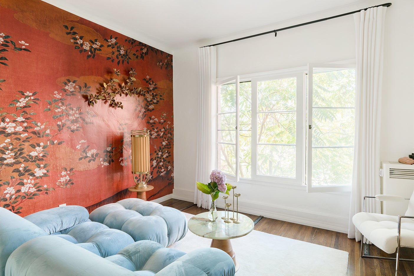 blue sofa in room with red floral wallpaper