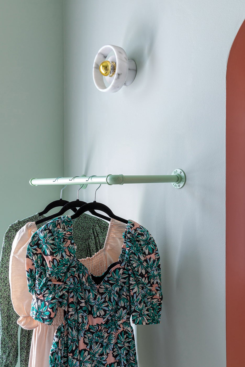 clothes hanging on mint green painted pipe