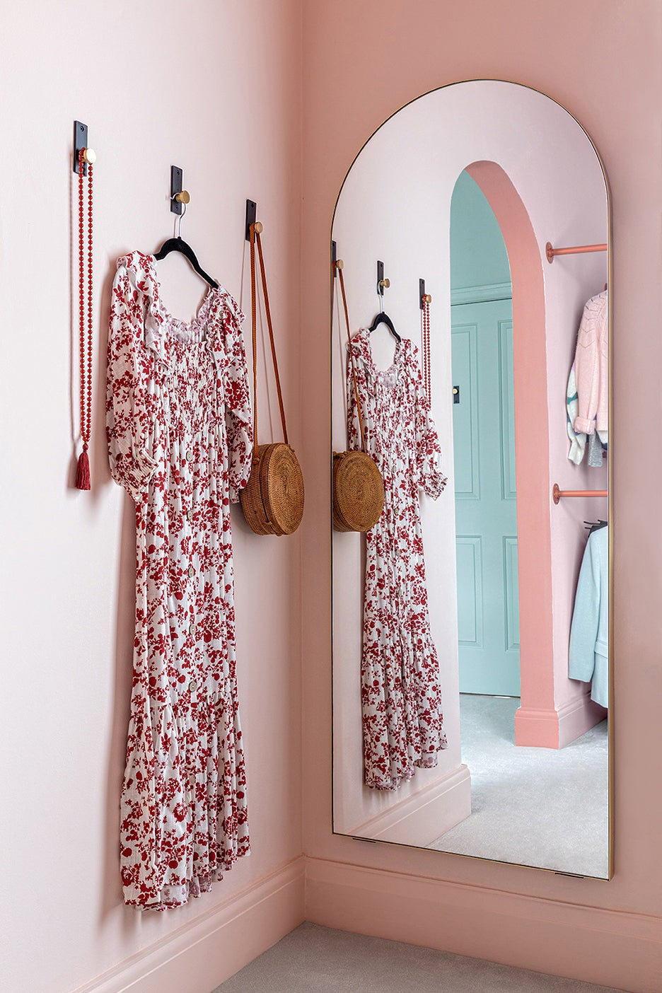 pink room with dress on a hook and arched mirror