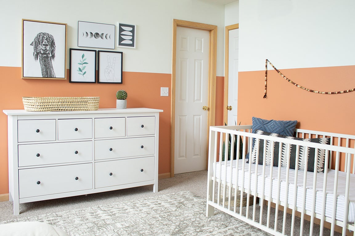 Terracotta rooms - white crib with peach mural on wall
