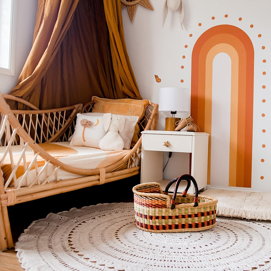 Terracotta rooms - bed with a fabric hanging and painted mural