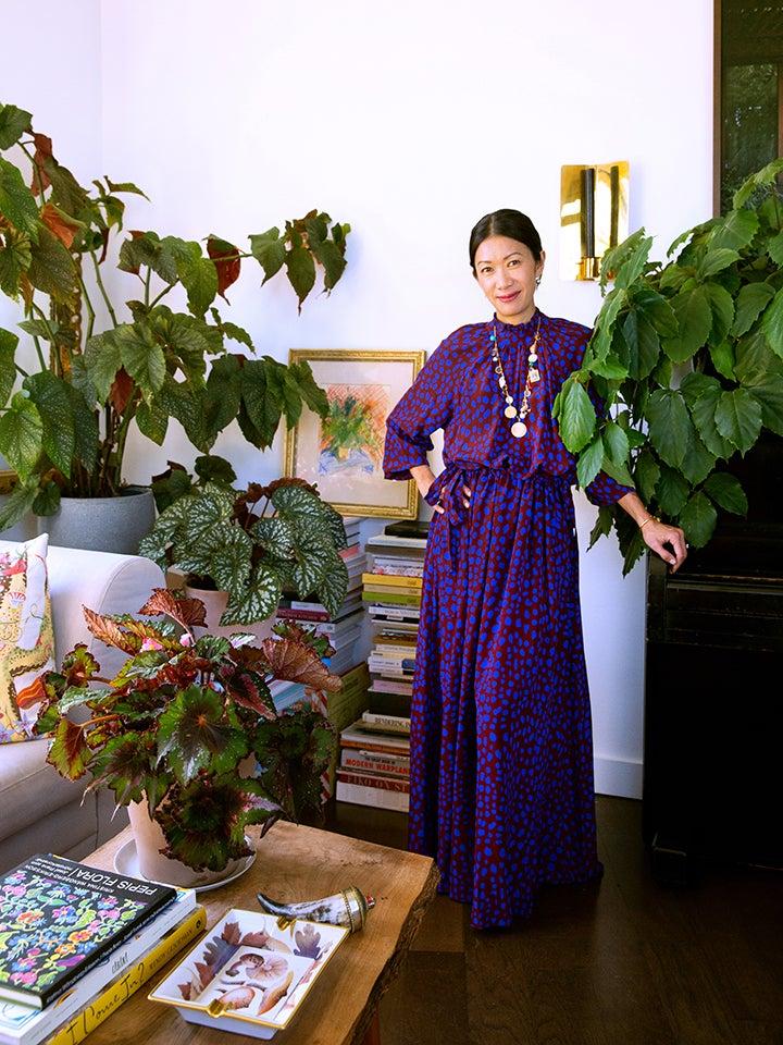 Woman in purple dress surrounded by houseplants