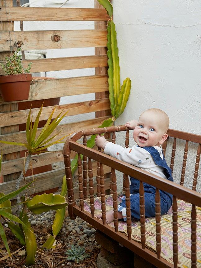 Baby in crib in backyard garden