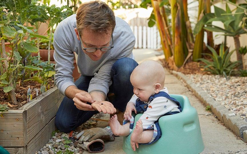 Dad showing baby seeds in backyard garden