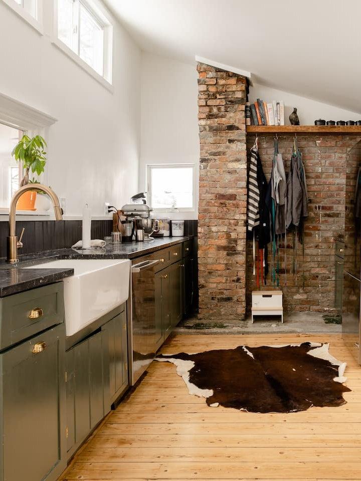 brick wall in green kitchen