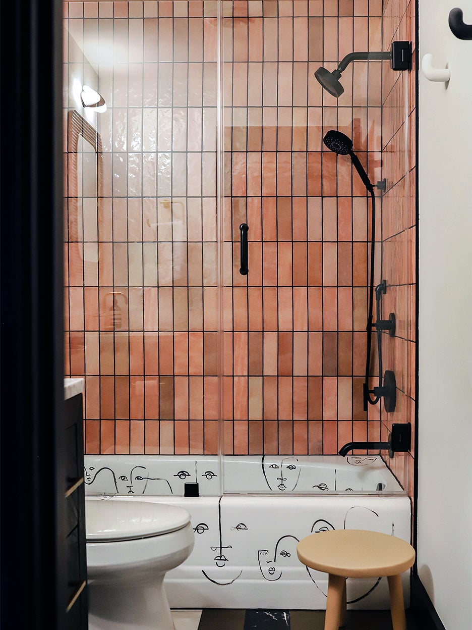 pink tiled shower with artful tub
