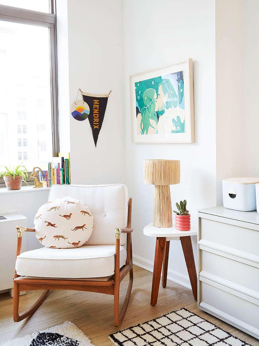 wood and white rocker surrounded by art