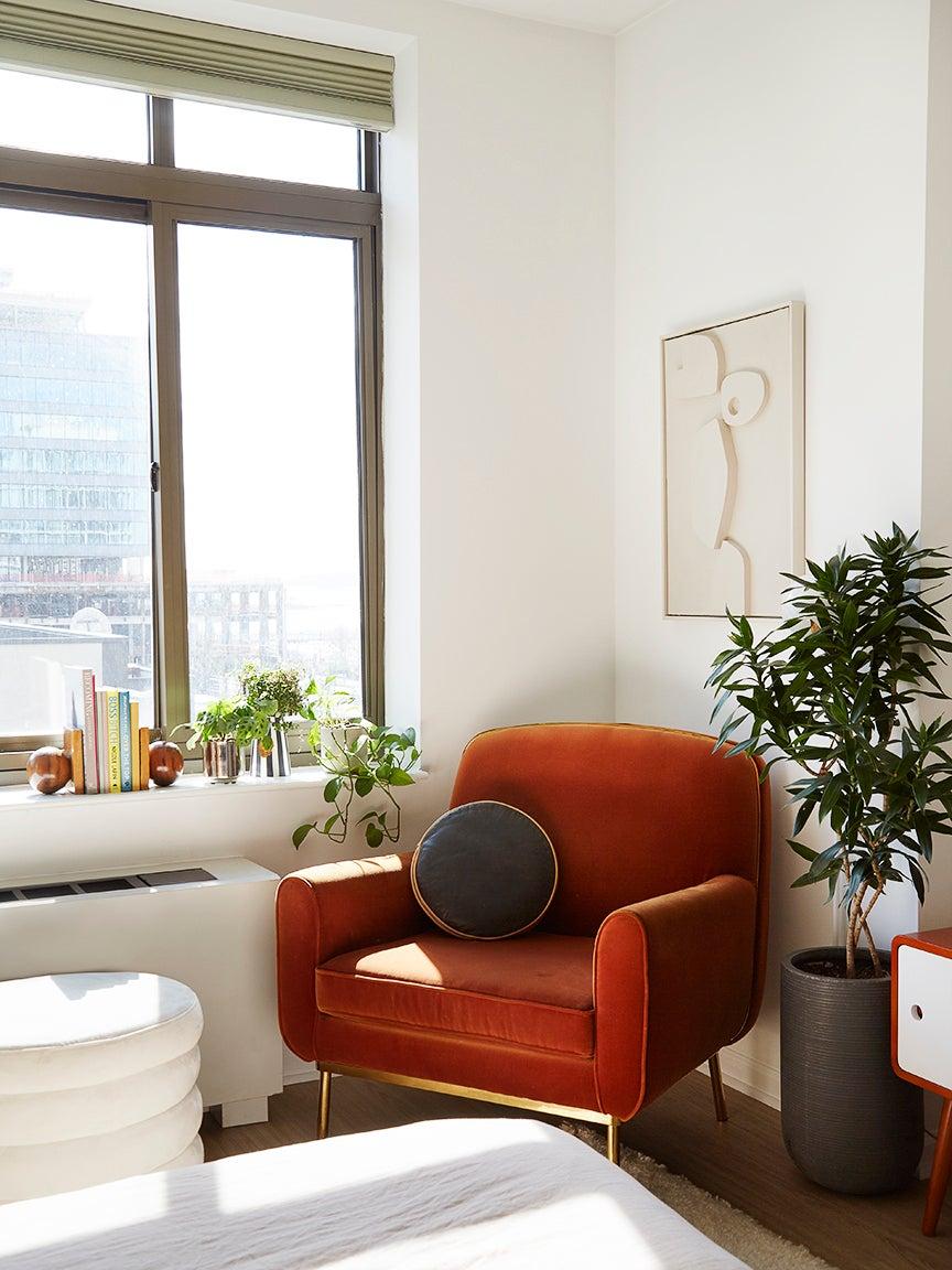 orange velvet chair in corner of bedroom