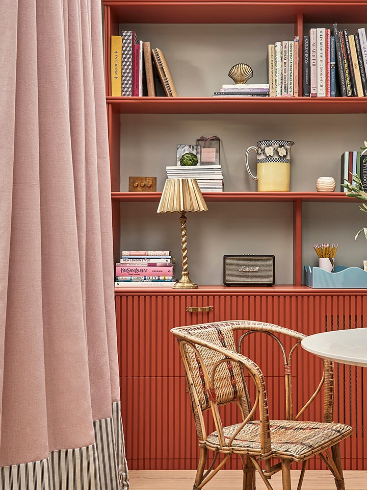 Red living room cabinet with a pleated lampshade on it