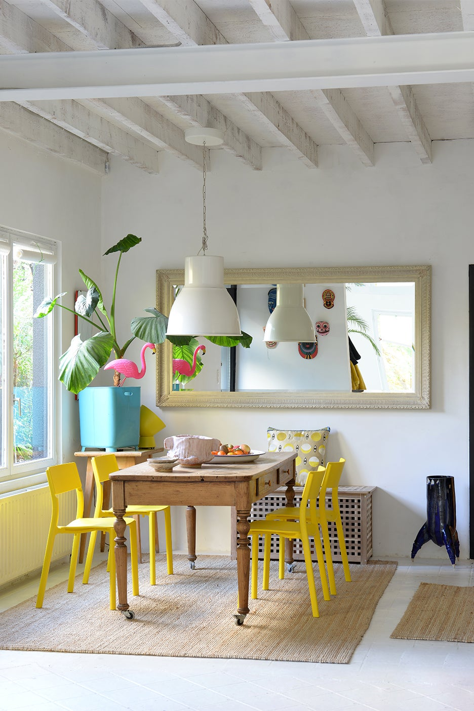 a dining room with yellow chairs