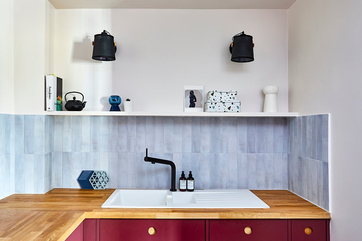sink with gray backsplash and open shelf