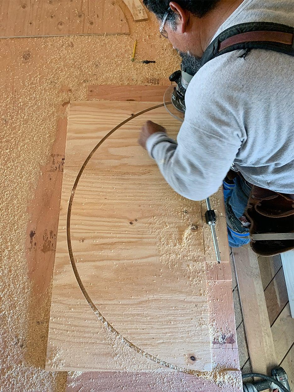 man cutting arch in wood
