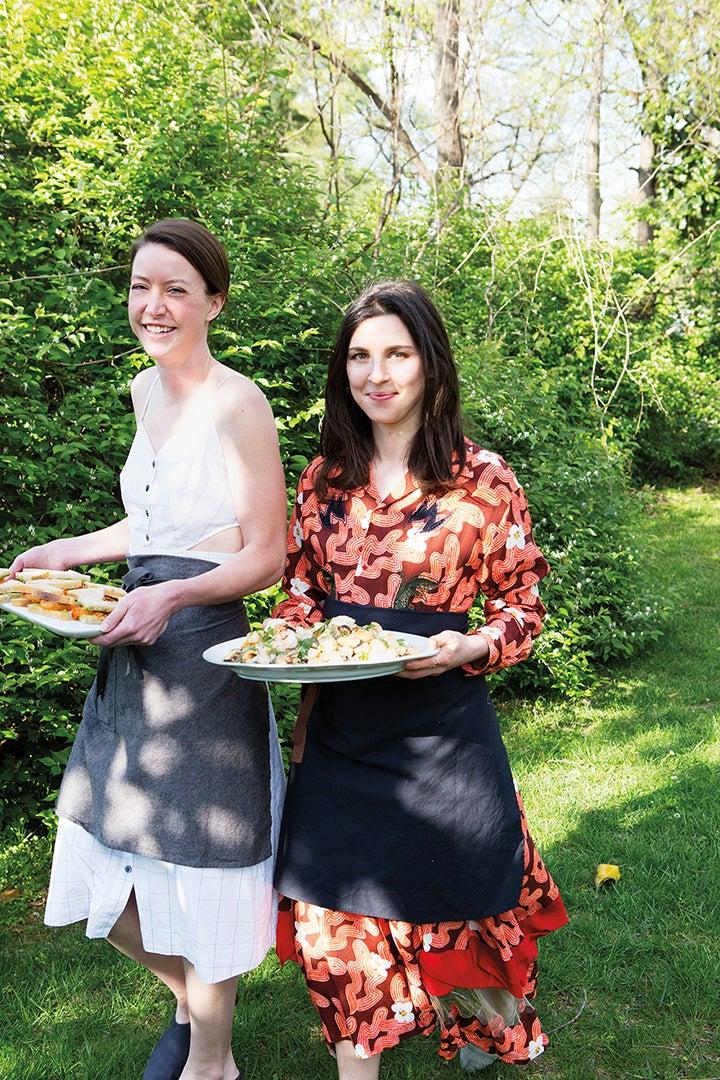 women walking in yard with food