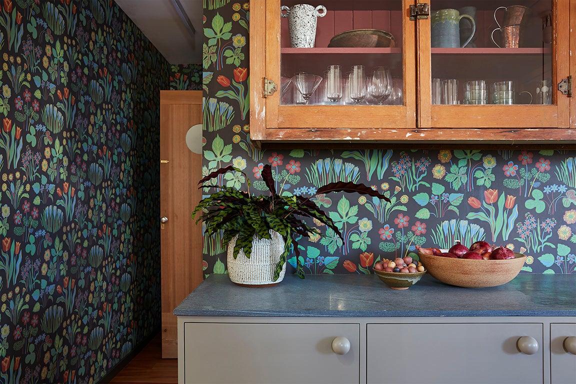 gray-brown bar cabinet with floral wallpaper backsplash