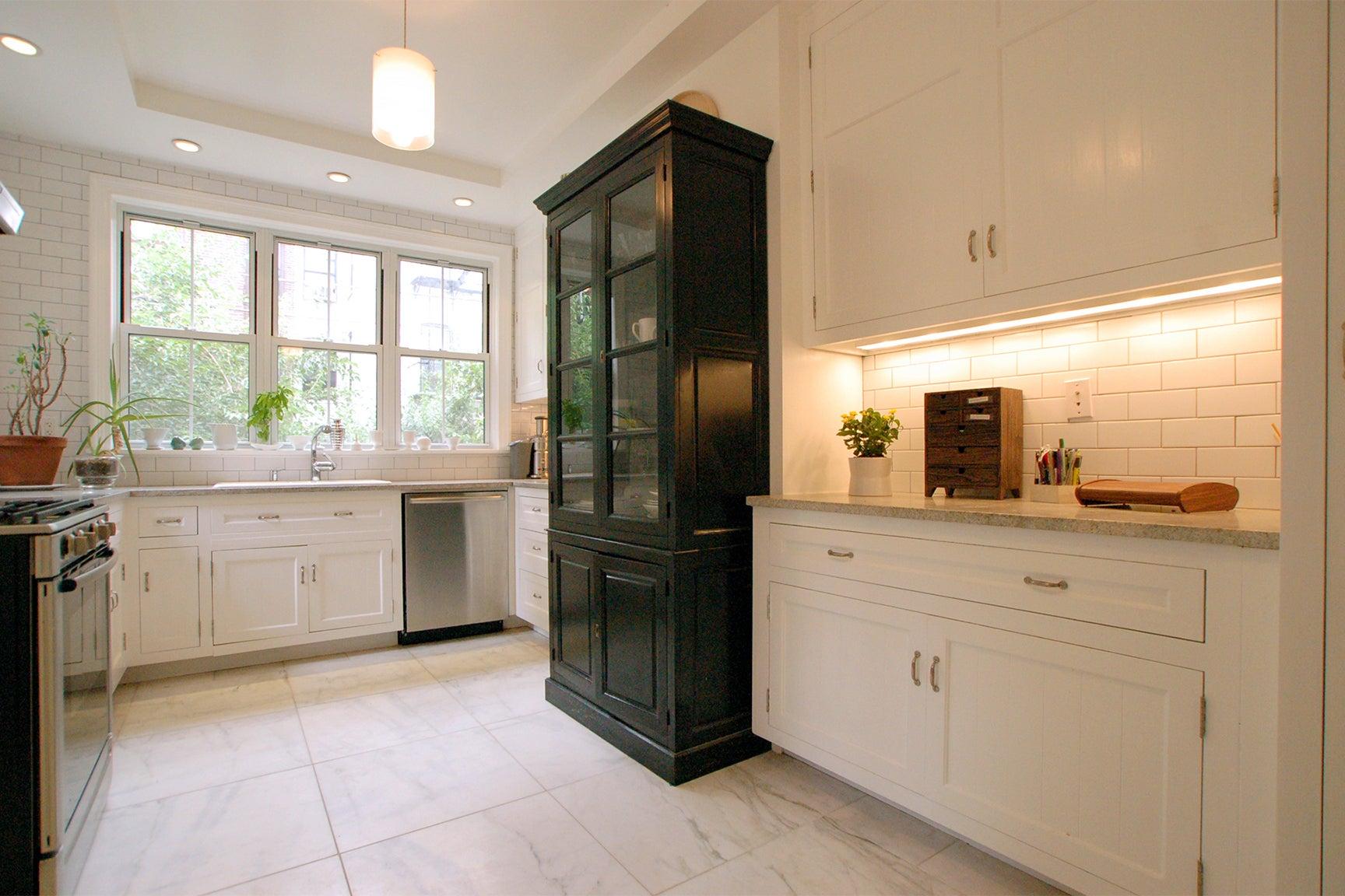 white kitchen with one dark storage cabinet