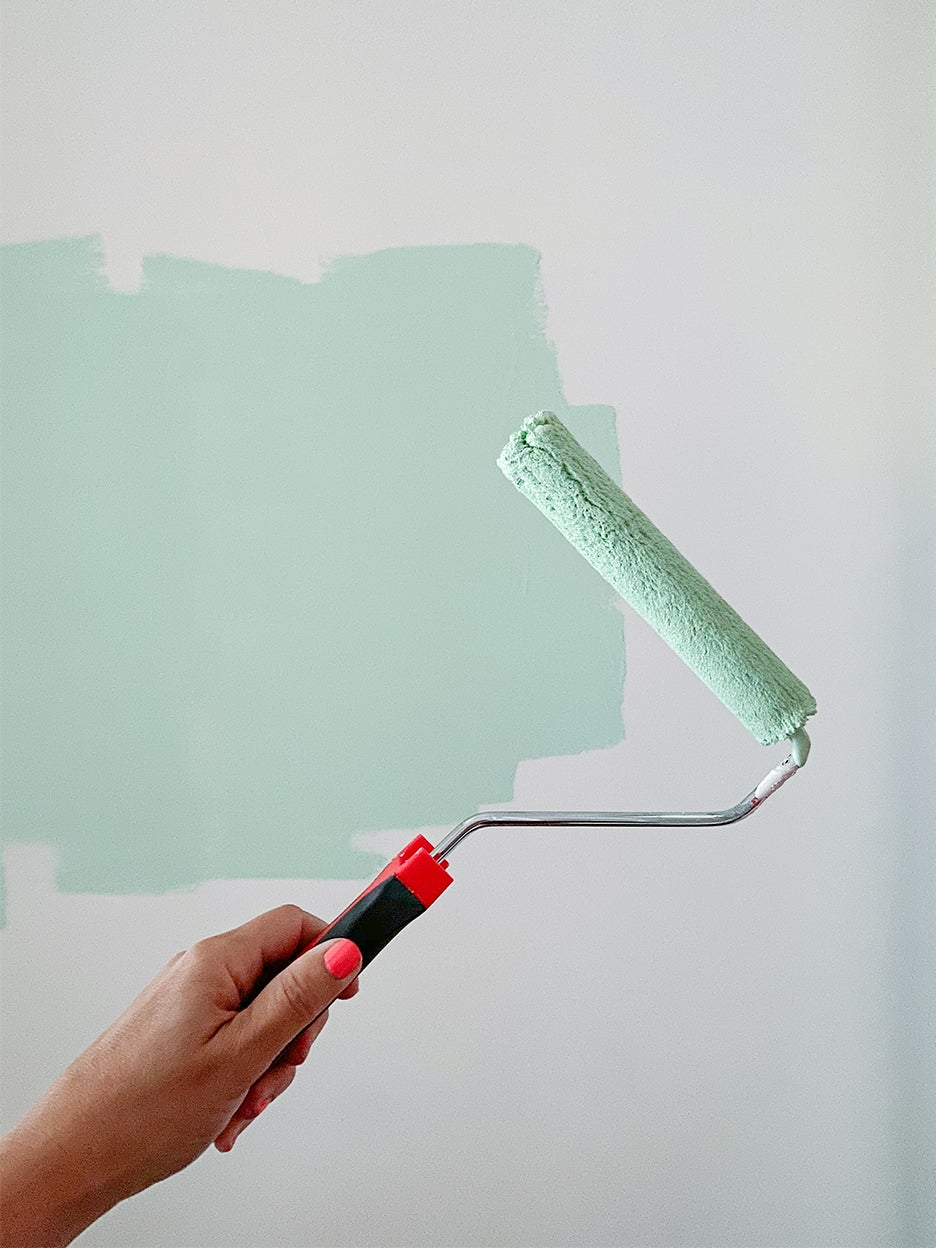 womans hand holding paint roller